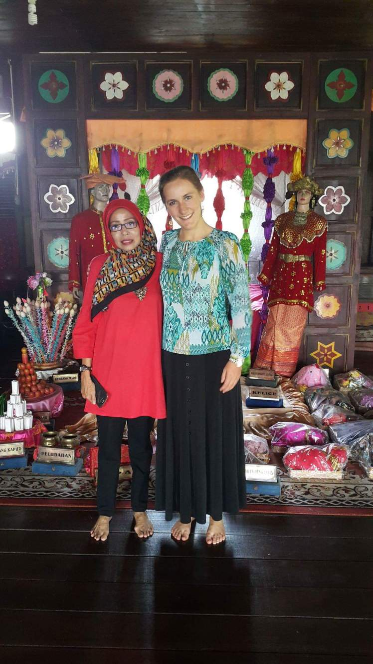 With Ibu Evi in front of an assortment of cultural artifacts in Belitung's Rumah Adat [Culture House].