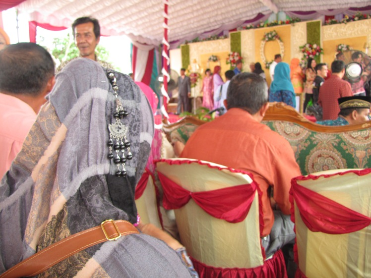 While we sit and nibble at our kue, we have prime viewing of the endless procession of greeters on stage. Indonesians get dressed up for weddings, and it is dazzling to see all of the bright colors and variety of styles on display.