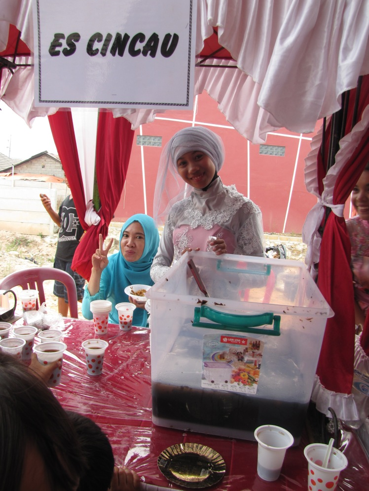 Es Cincau is a dark brown drink that has ice and mysterious, wiggling brown jelly strands. It tastes like it might be a distant relative of chocolate but it is hard to say for sure. Lya, wearing a blue hijab and a friend of Caitlin and I, is helping serve up cup after cup of Es Cincau.