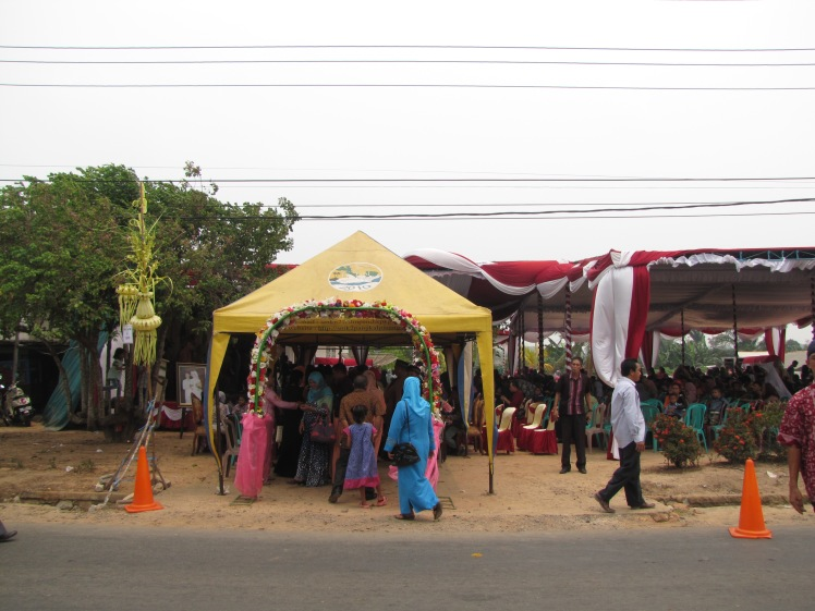 The welcoming archway as Despri and Nisa's wedding. Family members are waiting to greet guests under the yellow pop-up tent. The couple and their parents are sitting on a stage immediately to the left under the big tent, and rows and rows of chairs are set up facing the tent so that guests can people-watch while consuming massive amounts of food from the heavily laden buffet tables that line the perimeter of the big tent.