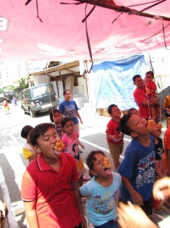 These kids are participating in a kerupuk-eating contest. The kerupuk are crackers that are on a string, and no hands are allowed. The first to get all the kerupuk off the string wins.