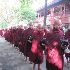 Myanmar's largest procession of monks walking out to take their daily alms.