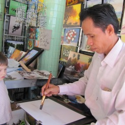 A young boy watches, transfixed, as an artist creates a surreal landscape with a few deft strokes of his brush.